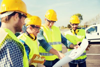 group of smiling builders in hardhats with clipboard and blueprint outdoors