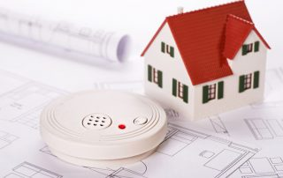 Smoke detector with house model on top of blueprints