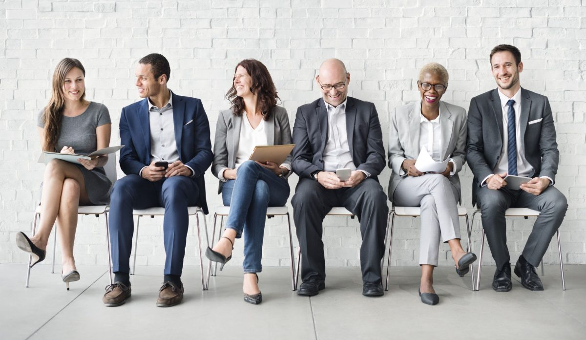 People dressed in business attire sitting in line for an interview