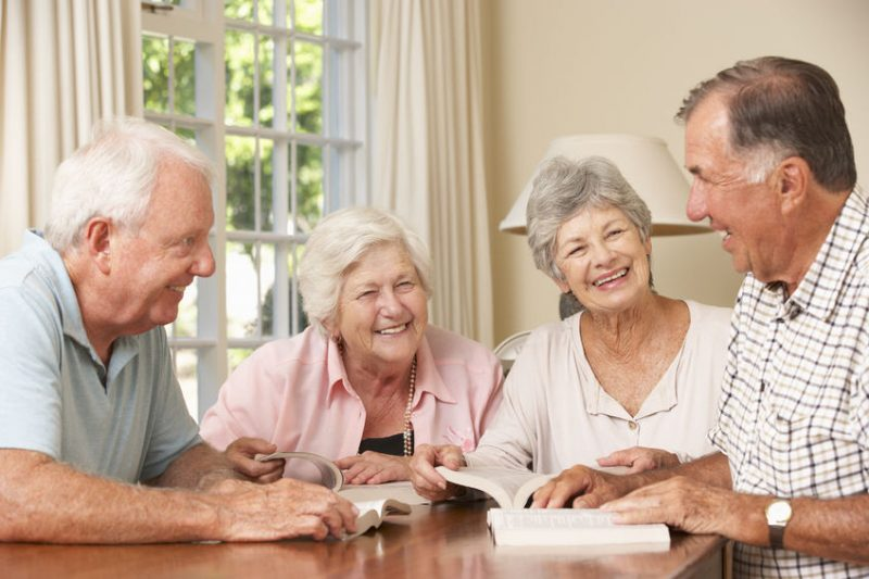 Senior citizens sitting in a reading group