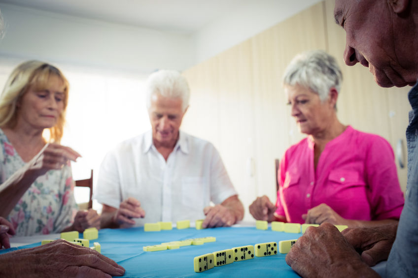 Group of seniors playing dominoes in the senior center