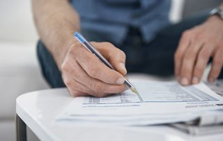 Person looking at billing statement with a pen in their hand