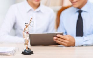 little statue of justice standing on the table with two professional lawyers working on the background