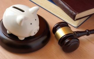 Piggy bank, gavel and books on a table