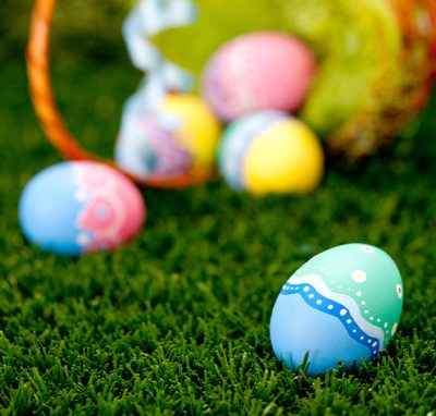 Colorful easter eggs and basket on the grass