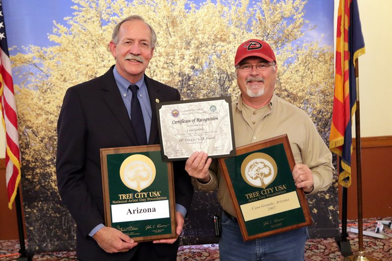 Two men holding up Tree City USA 10th year commemoration plaques