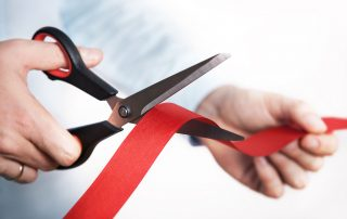 Red ribbon cutting with scissors