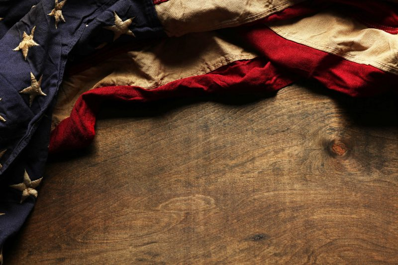 Wooden table top with an old rustic american flag laying on it